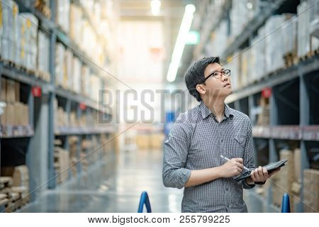 Young Asian Man Worker Doing Stocktaking Of Product In Cardboard Box On Shelves In Warehouse By Usin