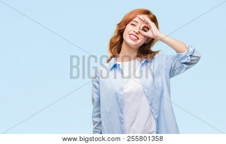 Young beautiful business woman over isolated background doing ok gesture with hand smiling, eye looking through fingers with happy face.