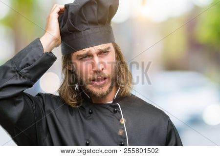 Young handsome cook man with long hair over isolated background confuse and wonder about question. Uncertain with doubt, thinking with hand on head. Pensive concept.