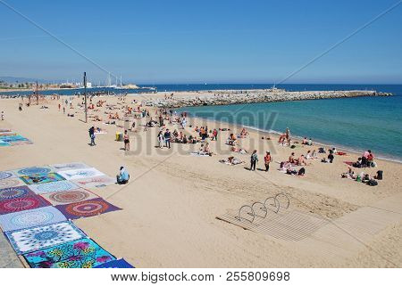 BARCELONA, SPAIN - APRIL 17, 2018: A blanket seller on the beach of the Capital of Catalonia.