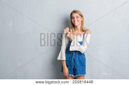 Beautiful young woman standing over grunge grey wall cheerful with a smile of face pointing with hand and finger up to the side with happy and natural expression on face looking at the camera.