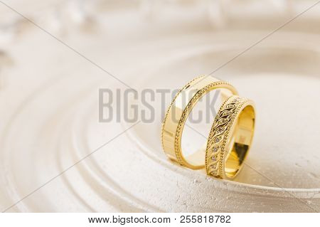 Two Gold Wedding Rings On Beige Background. Yellow Gold Rings With Ornament And Diamonds