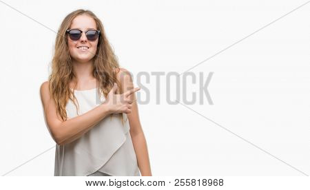 Young blonde woman wearing sunglasses cheerful with a smile of face pointing with hand and finger up to the side with happy and natural expression on face looking at the camera.