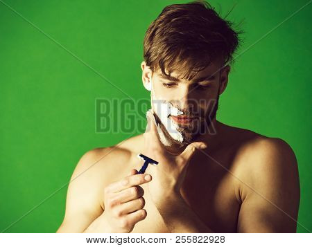 Man Or Bearded Macho With Naked Shoulders Shaving Beard Hair With Safety Razor And White Foam Or Cre