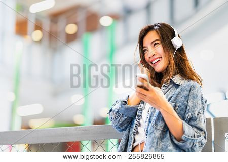 Beautiful Young Asian Girl Listen To Music Using Smartphone And Headphone Smile At Copy Space. Moder