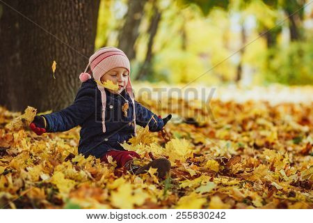 Family, Childhood, Fall Season And People Concept, Happy Girl Playing With Autumn Leaves In Park.lit