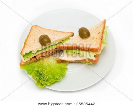 two cheeseburgers with olives on a plate