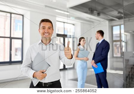 real estate business, sale and people concept - happy smiling realtor or businessman with folder showing thumbs up and customers at new office room