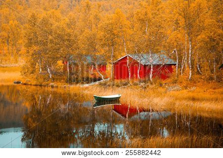 Finland. Fall Scene. Autumnal Landscape. Colorful Yellow Trees By The Lake With Fishing Boat. Fishin