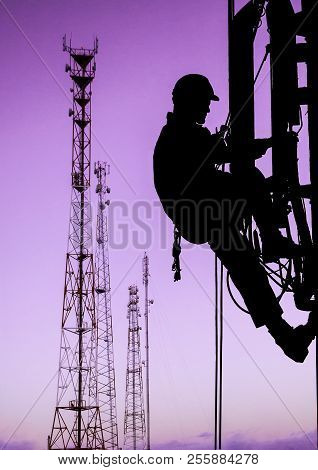 Silhouette Of Professional Industrial Climber In Helmet And Uniform Works At Height For Instaling Co