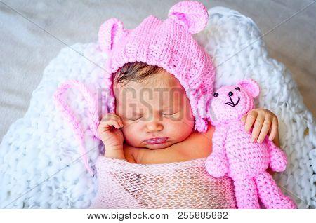 Sweet Caucasian Newborn Baby Girl In A Cute Pink Hat With Ears Hugging A Teddy Bear. Newborn Photo S