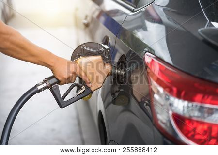 Pumping Gasoline Fuel In Car At Gas Station Pump, Refueling Fossil Fuel. Hand Holding Fuel Nozzle In