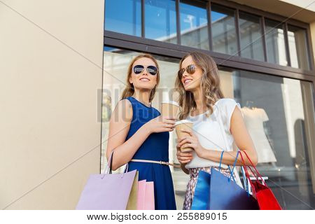 sale, consumerism and people concept - happy young women with shopping bags and coffee takeout at storefront