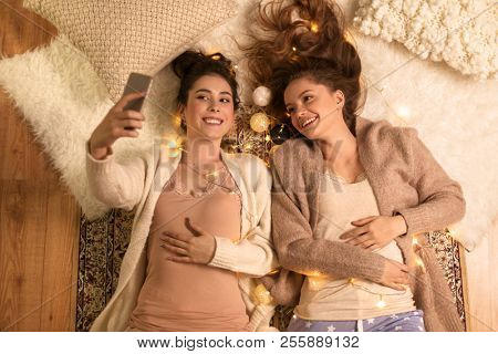 hygge, christmas and technology concept - happy female friends or teenage girls taking selfie by smartphone lying on floor with garland at home