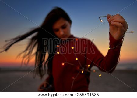 Teen Girl With Lights On Beach In Summer