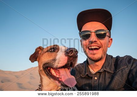 Funny Best Friends Concept: Human Taking A Selfie With Dog. Happy Young Male Person Makes Self Portr