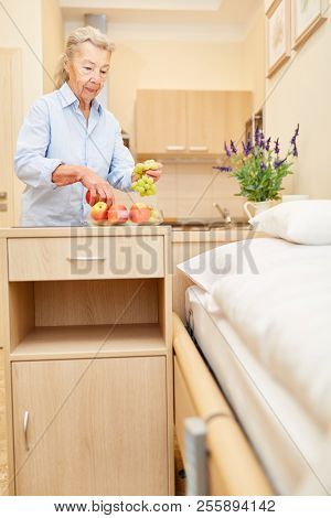 Old woman with fresh fruit in her senior citizen apartment in a senior residence