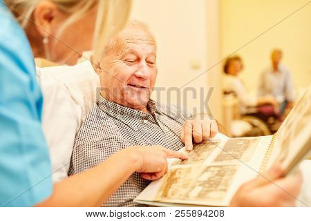 Senior man with dementia looks at photos together with caregiver in nursing home