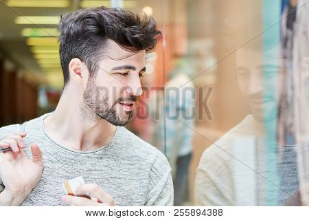 Young man in shopping mall while shopping in front of a shop window