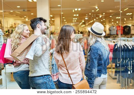 Young people shopping in the mall in front of a fashion shop