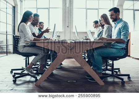 Young Smiling Business People Working On Laptops. Group Of Young Coworkers Sitting Together At Table