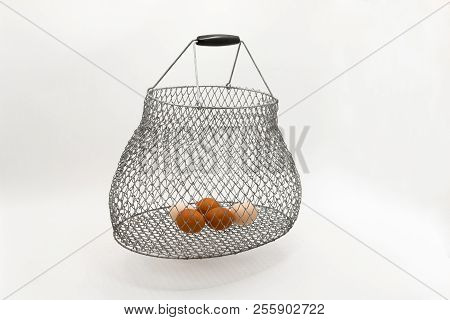 Still Life With A Metal Mesh And Chicken Eggs On A White Background.