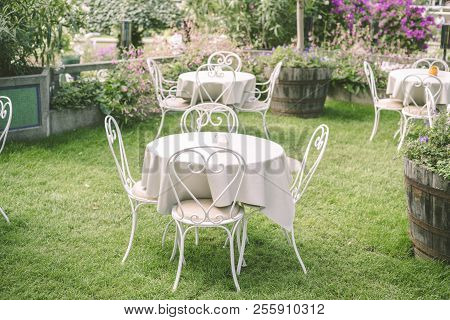 Romantic Garden Setting With Vintage Furniture And Table Cloth Surrounded By Flowers