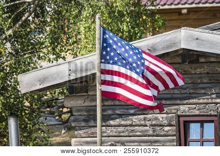 The Flag Of Usa Outside A Wooden Cabin In The Wild West
