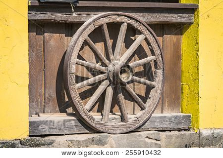 Wooden Wheel From A Prairie Wagon Standing Up Against A Yellow Wall