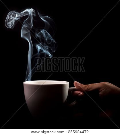 Fragrant coffee on a black background for your advertising. Smoke from hot coffee. A cup of fragrant coffee in hand.