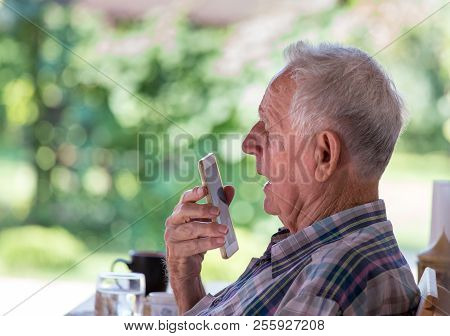Senior Man Sitting In Park And Talking On Cell Phone