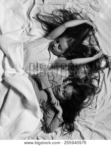 Schoolgirls In Pink Pajamas Wallow On Colorful Pillows, Top View. Childhood And Morning Concept. Kid