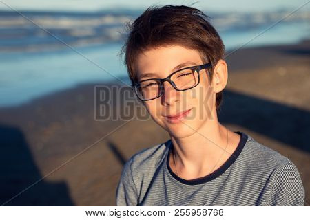 Young boy posing at the summer beach. Cute spectacled smiling happy 12 years old boy at seaside, looking at camera. Kid's outdoor portrait over seaside.