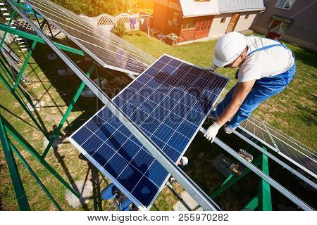 Mounter Installing Solar Panels On Green Carcass. Innovative Solution For Electricity Saving, Using