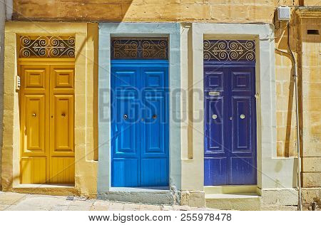 The West Street Boasts Numerous Historical Buildings With Traditional Wooden Doors, Covered In Brigh