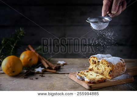 Sieving Powdered Sugar On A Christmas Cake, In Germany Christstollen, Orange And Spices Blurred In T