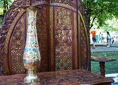 Gilded vase with floral ornament on the table made of mahogany. poster