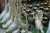 Silver decorative figurines and black vases with gilded ornaments. poster