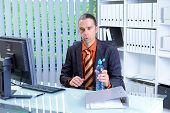 business man with water bottle at his desk in summerly hot office poster
