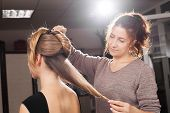 professional hairdresser making an unusual coiffure with a bun to a brown haired young model in a beauty salon poster