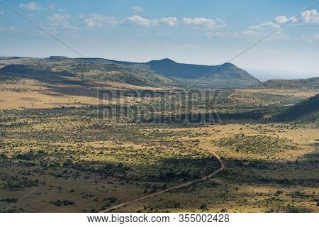 The Plains Of Endless Arid Bush Landscape Stretching Out Towards Hills On The Horizon, With A Single