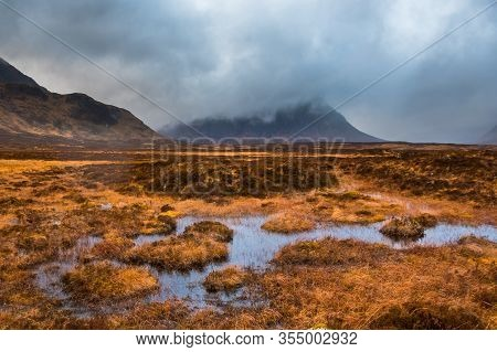 Buachaille Etive Mor Shrouded In Clouds With Marshy Water And Grass In The Foreground. Glencoe, Scot