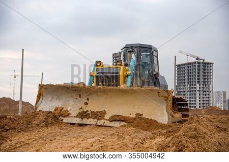 Bulldozer During Land Clearing And Foundation Digging At Large Construction Site. Crawler Tractor Wi