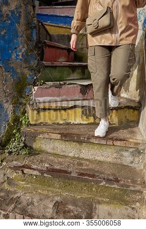 An Old Spiral Staircase Made Of Concrete With Faded Rainbow Colors, A Woman Tourist Descends The Sta