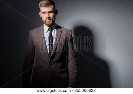 Studio Portrait Of A Young Bearded Handsome Guy Of Twenty-five Years Old, In An Official Suit, Looki