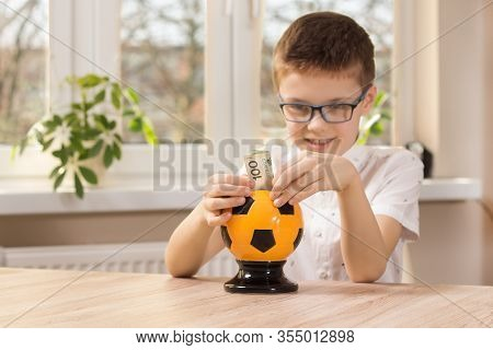 School-age Boy With Glasses Sitting At The Table. He Holds A 100 Zloty Banknote In His Hands Which H