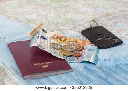 A Paper Road Map With A Passport, Euro Banknotes And Coins And A Car Card.
