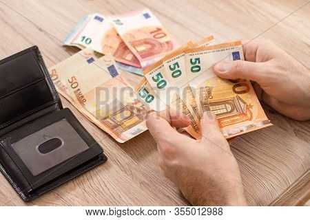 Male Hands Arrange Euro Cash On The Table. A Black Leather Wallet Lies On The Table.