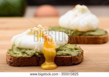 Leaking Poached Yolk. Sandwiches With Poached Egg And Avocado Paste On Cereal Bread. Healthy Lifesty