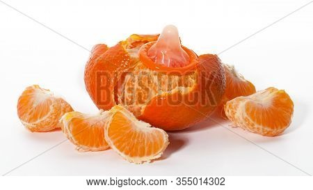 Unwrapped Color Condom With Fruit Flavor And Peeled Tangerines On White Background. Macro Shot. Safe